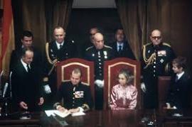 La transición a la democracia, pilotada por un nuevo equipo, comenzó con la Ley de Reforma Política en 1976. En mayo de 1977, el Conde de Barcelona transmitió al Rey sus derechos dinásticos y la Jefatura de la Casa Real española, en un acto que constataba el cumplimiento del papel que correspondía a la Corona en el retorno a la democracia. Un mes más tarde se celebraron las primeras elecciones democráticas desde 1936, y el nuevo Parlamento elaboró el texto de la actual Constitución, aprobada por referéndum el 6 de diciembre de 1978 y sancionada por S.M. el Rey en la sesión solemne de las Cortes Generales del 27 del mismo mes y año.