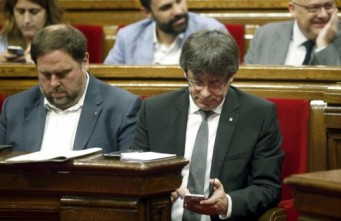 El presidente de la Generalitat, Carles Puigdemont (d), y su vicepresidente, Oriol Junqueras, durante el pleno del Parlament