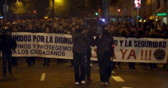 """La manifestación, convocada por sindicados y asociaciones de Mossos d'Esquadra, Guàrdia Urbana de Barcelona, Policía Nacional y Ertzaina, ha congregado a entre 1.500 agentes -según la Guàrdia Urbana- y 3.000 -según la organización-, que iban vestidos de negro, con un brazalete rojo en el brazo que les identificaba como policías y en silencio, que sólo rompía el estruendo de algunos petardos y música fúnebre. Los agentes llevaban una pancarta en la cabecera de la manifestación con el lema """"Todos unidos por la dignidad, el respeto y la seguridad. Servimos y protegemos a los ciudadanos. Basta ya"""".- (Más de mil policías piden a la CUP respeto institucional http://www.larazon.es/espana/mas-de-mil-policias-piden-a-la-cup-respeto-institucional-IE14329067?sky=Sky-Enero-2017#Ttt1lskvSGcI0rRX"""