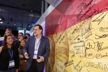 El presidente del Gobierno y líder del PP, Mariano Rajoy, firma en una bandera española a su llegada a la segunda jornada del XVIII Congreso nacional del partido http://www.larazon.es/fotogalerias/conclave-popular-DI14496410